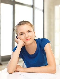 Foto di un'adolescente felice con carta e penna