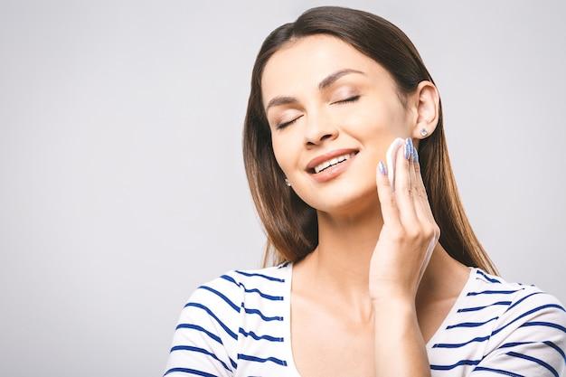 Una foto di una donna felice che pulisce il viso con tamponi di cotone
