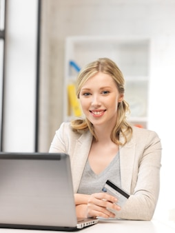 Foto di donna felice con computer portatile e carta di credito..
