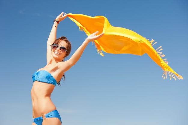 Foto di donna felice con pareo giallo sulla spiaggia.