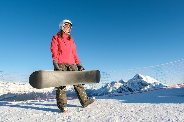 Maschera dello snowboarder felice della giovane signora sui pendii