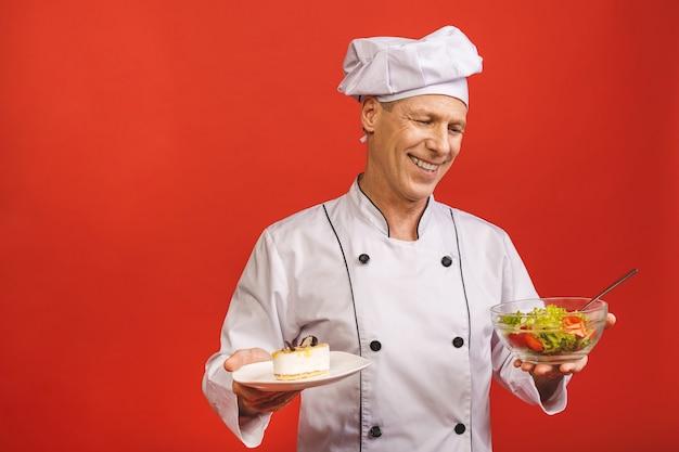 Immagine di giovane cuoco principale senior felice nella condizione dell'uniforme isolata sopra il fondo rosso della parete, tenendo insalata e il dolce. concetto di dieta.