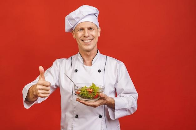 Immagine di giovane cuoco principale senior felice nella condizione dell'uniforme isolata sopra il fondo rosso della parete, tenente insalata.