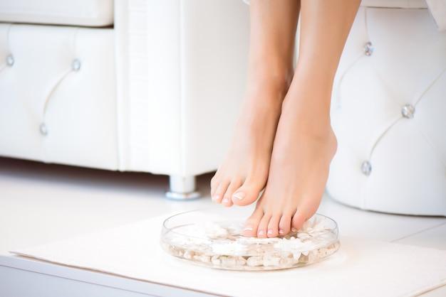 L'immagine della manicure e pedicure ideale. piedini femminili nel punto della stazione termale.