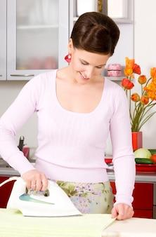 Immagine della donna che stira in cucina