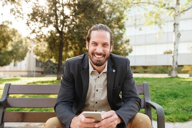 Foto di gioioso bell'uomo con i capelli legati alla ricerca e tenendo il cellulare, mentre è seduto su una panchina nel parco cittadino durante la giornata di sole