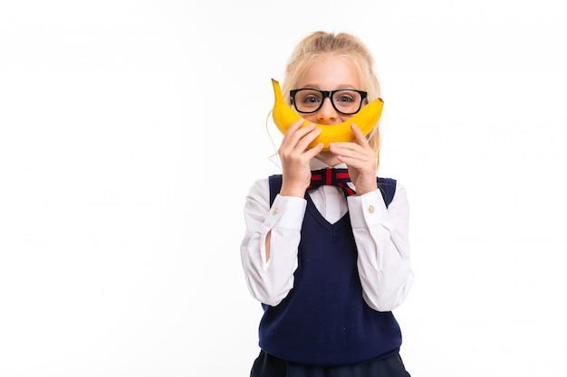 L'immagine di una bambina con capelli biondi tiene una banana e sorride con esso