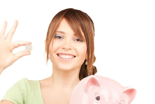 Foto di una bella ragazza adolescente con salvadanaio e moneta