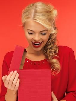 Foto di una bella donna vestita di rosso con una confezione regalo aperta