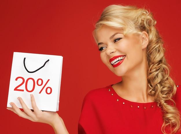 Foto di una bella donna in abito rosso con borsa della spesa