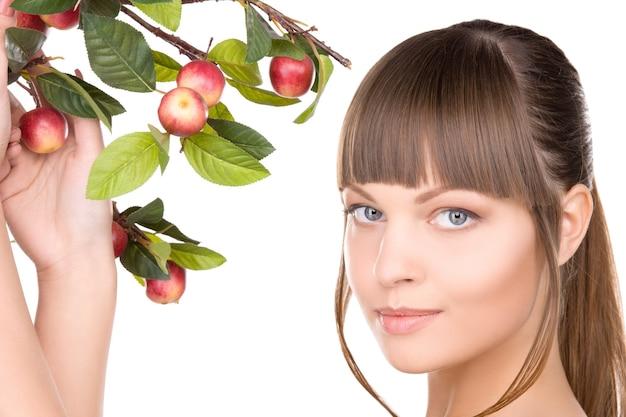 Foto di una bella donna con un ramoscello di mele apple