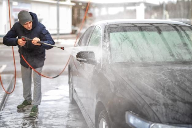 Una foto di un uomo che lava un'auto all'aperto sotto l'alta pressione nella stagione fredda.