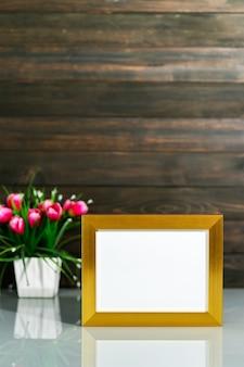 Picture mock up con cornice dorata e bouquet di vasi di fiori artificiali sul tavolo con sfondo di parete in legno