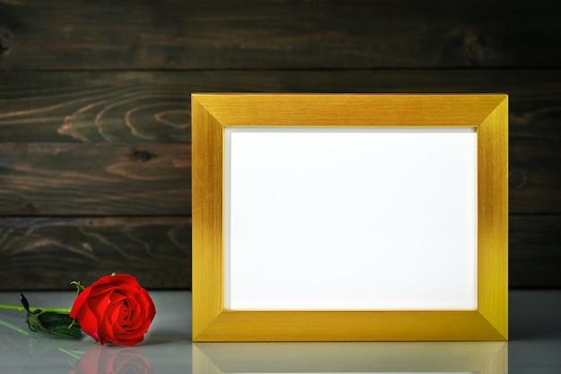 Foto mock up con cornice dorata e fiori di rose rosse sul tavolo con spazio di copia