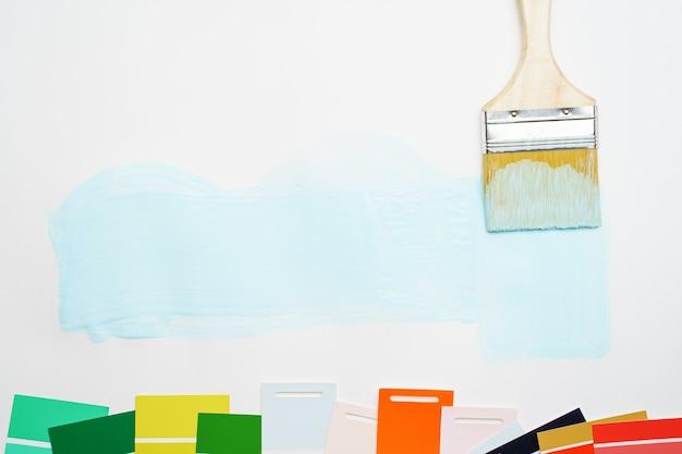 Immagine della tavolozza con colori blu e verde, rosso, pennello, su sfondo bianco vuoto. posto per il testo.