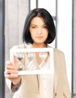Foto di una donna d'affari pensierosa con un bicchiere di sabbia