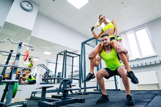 Foto di personal fitness trainer e cliente femminile in palestra in posa davanti alla telecamera. vita sana e concetto di fitness. la ragazza si siede sulla spalla dell'uomo coccolandole i capelli.
