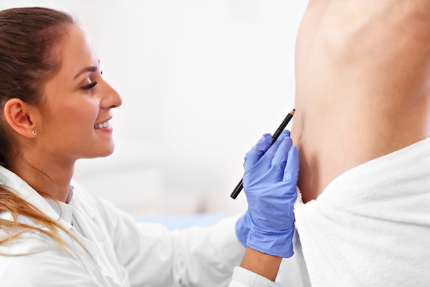 Immagine del chirurgo plastico che fa segni sul corpo del paziente