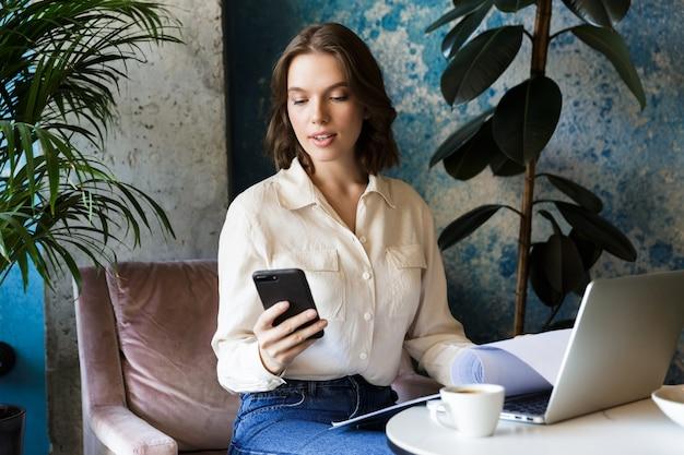 Foto di bella giovane donna seduta in un caffè al chiuso lavora con il computer portatile che tiene i documenti utilizzando il telefono cellulare.