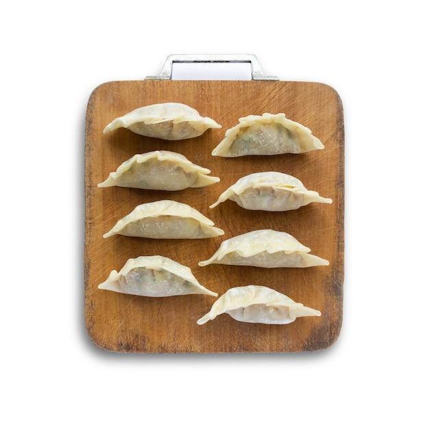 Immagine di gnocchi crudi o gyoza su tagliere di legno isolato su sfondo bianco