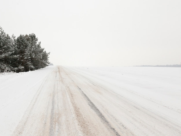 Immagine della strada nella stagione invernale. primo piano, sulle strisce d'asfalto innevate visibili dai pneumatici dell'auto