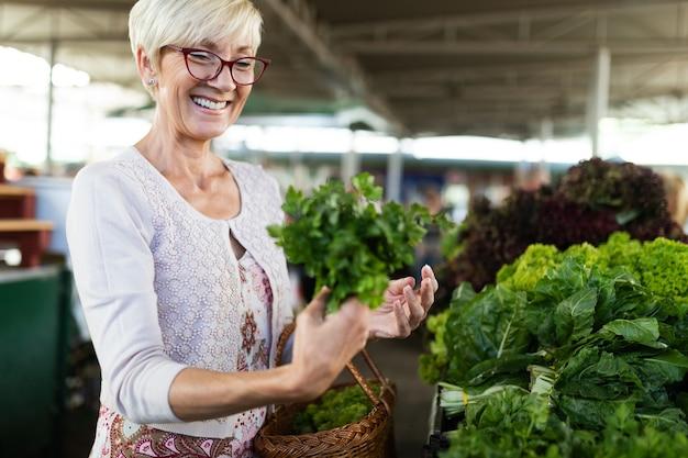Immagine di una donna anziana felice al mercato che compra frutta e verdura