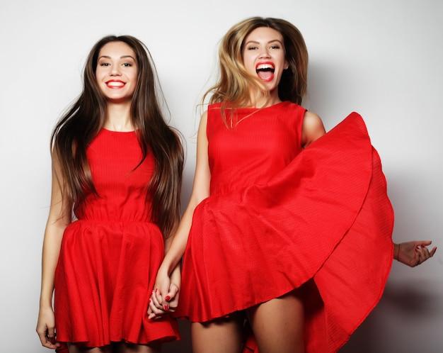 Immagine di ragazze sensuali in abito rosso su superficie bianca