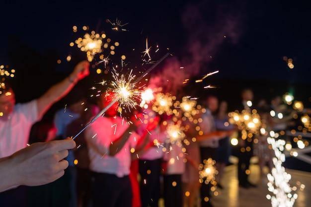 Immagine che mostra un gruppo di amici che si divertono con le stelle filanti.