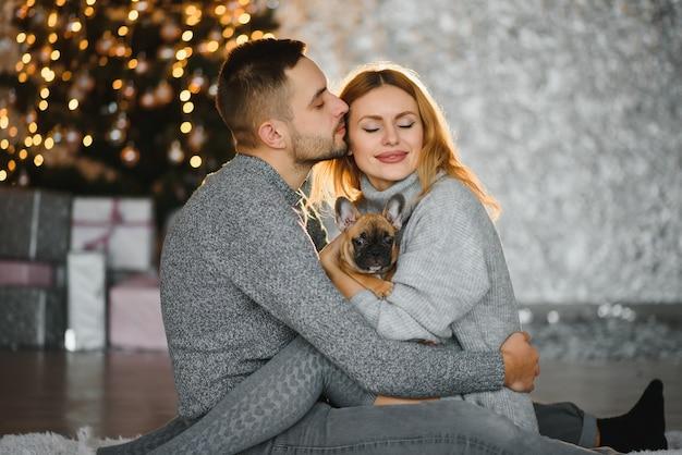 Immagine che mostra le giovani coppie che abbracciano sopra l'albero di natale