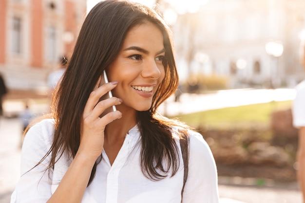 Immagine della donna castana sorridente in camicia che parla dallo smartphone