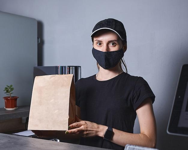 Immagine della donna sorridente del venditore con la maschera che sta dietro il registratore di cassa