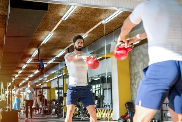 Foto di forte uomo sportivo concentrato sollevamento pesi in palestra. in piedi davanti allo specchio.