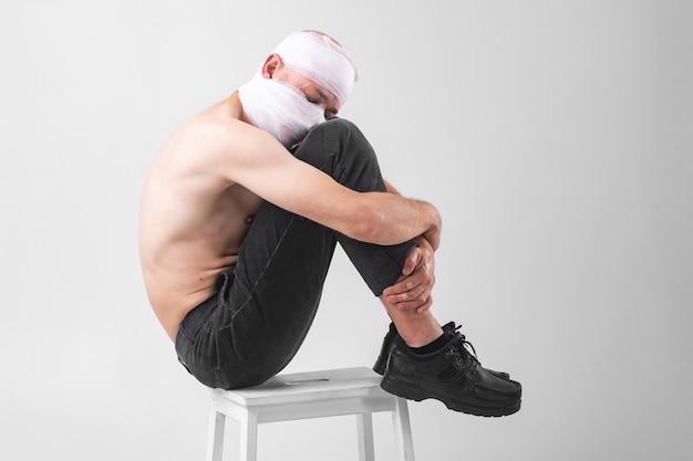 L'immagine del maschio di sofferenza con la testa bendata si siede su una sedia in studio