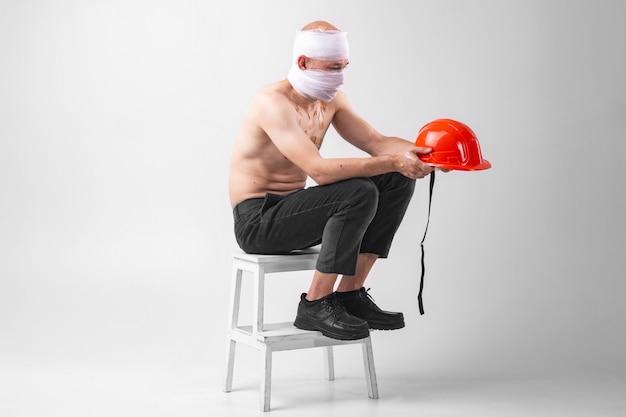 L'immagine del maschio sofferente con la testa bendata si siede su una sedia con il casco protettivo