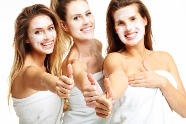 Immagine di tre amici nella spa che mostrano il segno ok
