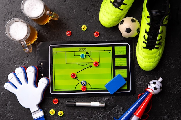 Immagine in cima a due boccali di birra schiumosa, calcio balilla, palla, scarpe da calcio, pipa, sonaglio sul tavolo nero