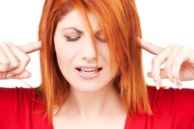Foto di donna infelice rossa con le dita nelle orecchie