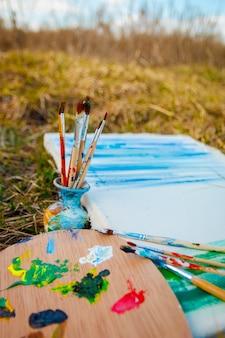 Foto con colori tavolozza e pennelli su sfondo erba.