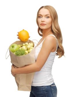 Foto di donna con borsa della spesa e arancia
