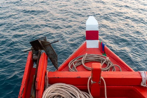 Una foto di una prua di un peschereccio in legno e dipinta di rosso, una barca da pesca galleggia nel mare, thailandia