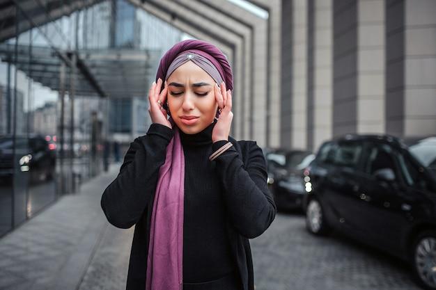 L'immagine di giovane donna araba sta fuori. tiene le mani vicino alla testa e tiene gli occhi chiusi. il modello ha mal di testa. lei soffre.