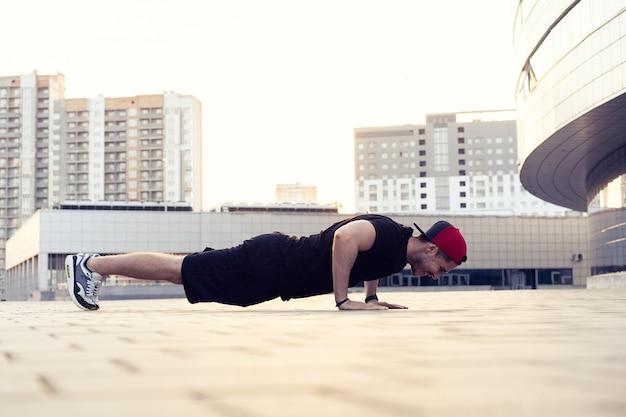 Foto di un giovane uomo atletico facendo push up all'aperto. fitness ed esercizio all'aperto ambiente urbano.