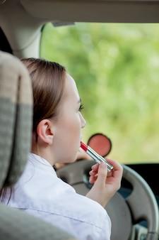 Immagine di una giovane donna d'affari che si trucca mentre guida un'auto nel traffico.