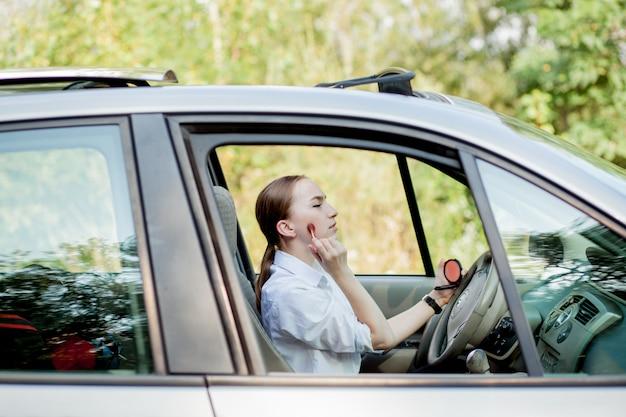 Immagine di giovane donna di affari che fa trucco mentre guidando un'automobile nell'ingorgo stradale