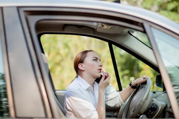 L'immagine di una giovane donna d'affari parla al telefono e si trucca mentre guida un'auto nel traffico.