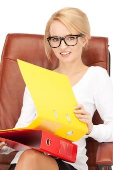 Foto di una giovane donna d'affari con le cartelle seduta su una sedia