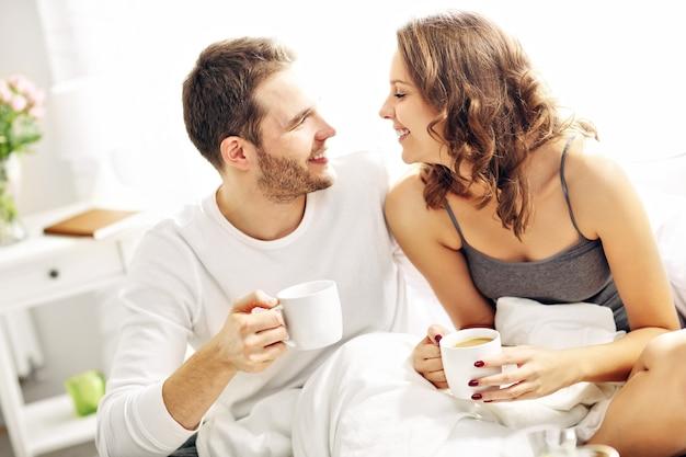 Immagine di una giovane coppia che beve caffè a letto
