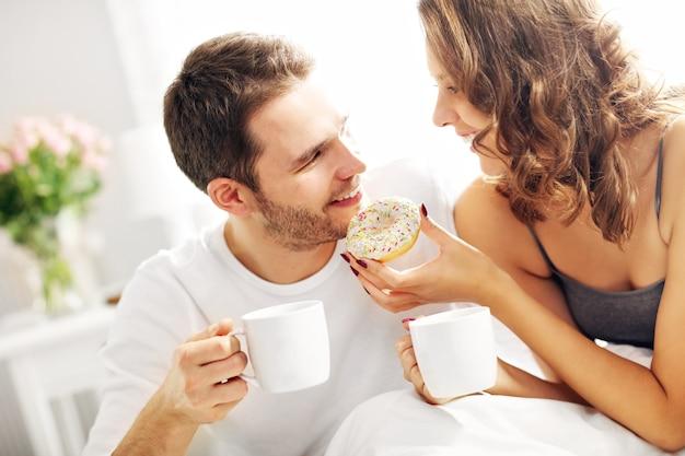 Immagine di una giovane coppia che fa colazione a letto