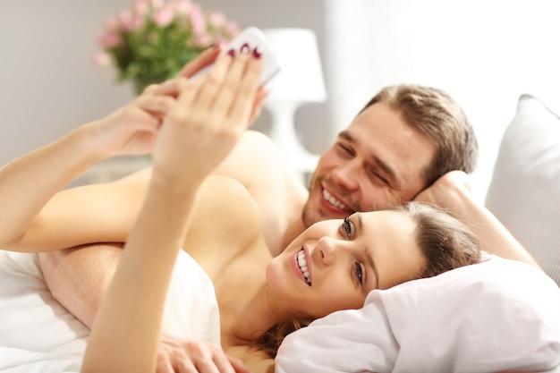 Immagine di una giovane coppia che si abbraccia a letto con lo smartphone