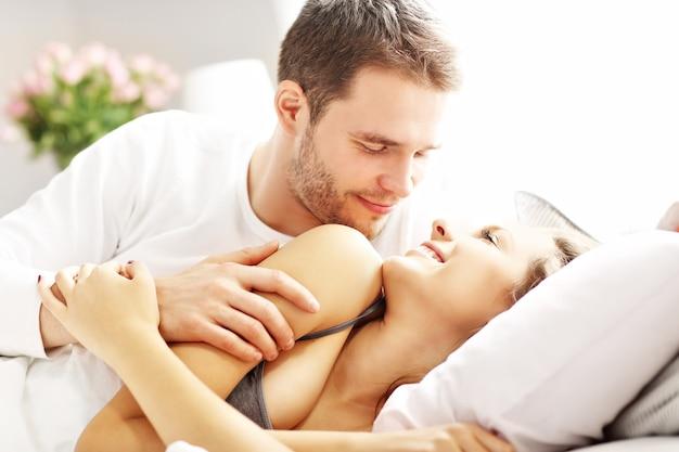 Immagine di una giovane coppia che si abbraccia a letto